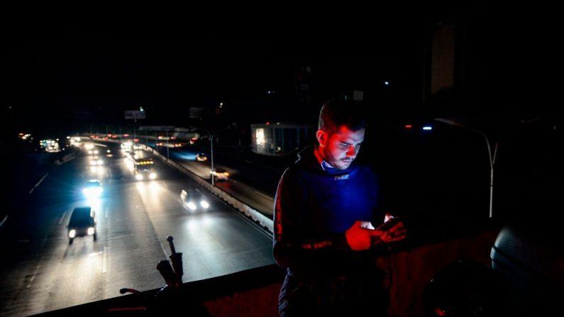 Un hombre revisa su teléfono móvil en Caracas el 22 de julio de 2019 mientras la capital y otras partes de Venezuela están siendo golpeadas por un corte de electricidad masivo. (MATIAS DELACROIX/AFP/Getty Images)
