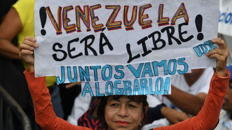 """Una mujer sostiene un cartel que dice: """"Venezuela será libre. Lo lograremos"""" ante una sesión de la Asamblea Nacional en la plaza Alfredo Sadel de Caracas el 23 de julio de 2019. (YURI CORTEZ/AFP/Getty Images)"""