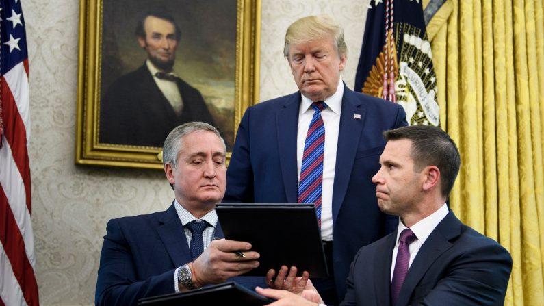 Donald Trump observa mientras el ministro del Interior de Guatemala, Enrique Degenhart (I), y el secretario interino de Seguridad Nacional de los Estados Unidos, Kevin K. McAleenan (D) intercambian documentos al firmar un tercer acuerdo de seguridad en la Oficina Oval de la Casa Blanca el 26 de julio de 2019 en Washington, DC. (Brendan Smialowski/AFP/Getty Images)