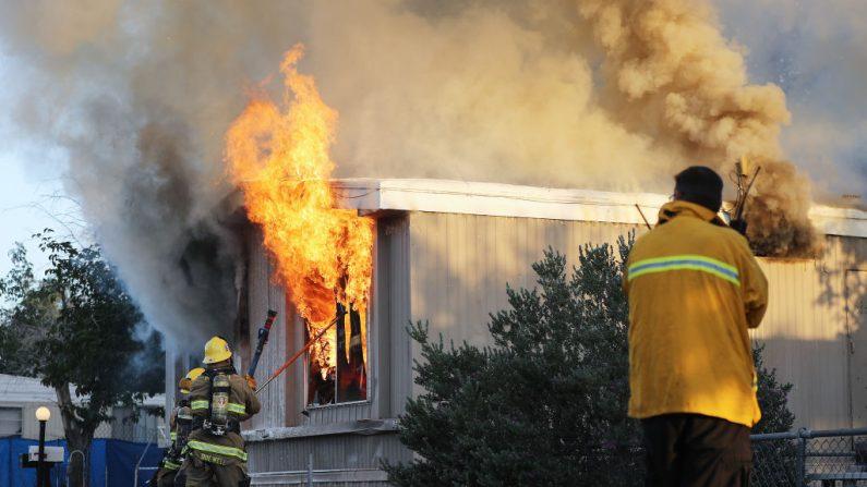 Los bomberos trabajan para apagar un incendio en la casa. (Crédito: ROBYN BECK/AFP/Getty Images)