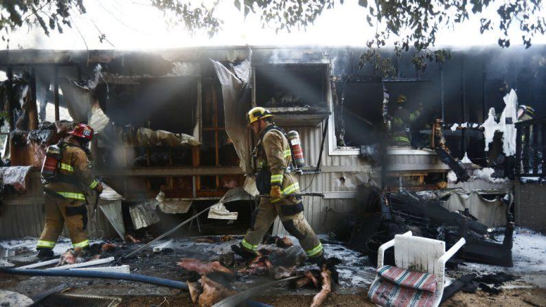 Visto la cerca de alambre, los bomberos trabajan para apagar un incendio en la casa, la mañana después de un terremoto de magnitud 7.1 que azotó el área, el 6 de julio de 2019 en Ridgecrest, California. El terremoto, ocurrido la noche del 5 de julio, fue el segundo terremoto más grande que azotó el área en dos días y el más grande en el sur de California en 20 años. (Mario Tama / Getty Images)
