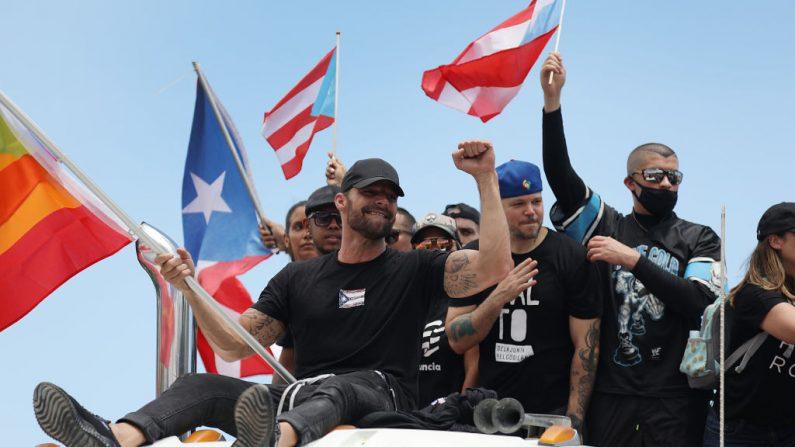Sobre un camión el cantante Ricky Martin, el rapero Residente y el rapero Bad Bunny (de izquierda a derecha) se une a miles de personas que llenan la carretera Expreso Las Américas para pedir la renuncia del gobernador Ricardo A. Rosselló el 22 de julio de 2019 en San Juan, Puerto Rico. (Joe Raedle/Getty Images)