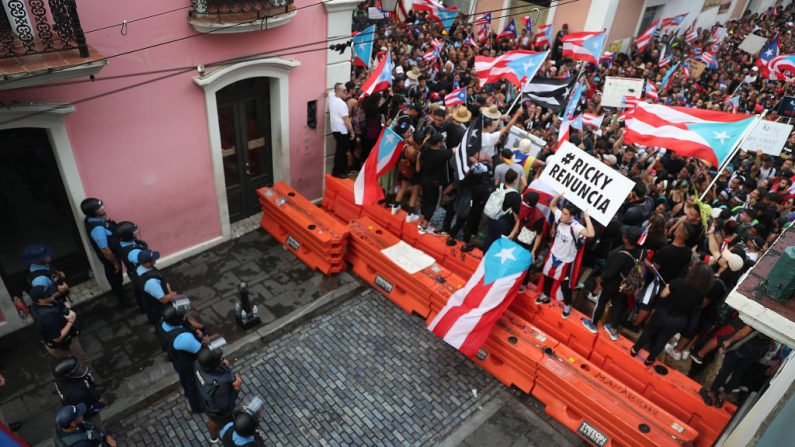 Los manifestantes en contra de Ricardo Rosselló, el Gobernador de Puerto Rico, cerca de la policía que está a cargo de una barricada instalada a lo largo de una calle que conduce a la mansión del gobernador el 22 de julio de 2019 en el Viejo San Juan, Puerto Rico. (Joe Raedle/Getty Images)