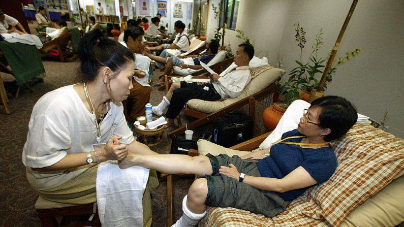 Unos masajistas tailandeses aplican el masaje tradicional de pies de forma gratuita a los miembros de los medios de comunicación que cubrirán la cumbre de la Cooperación Económica Asia-Pacífico (APEC) en Bangkok, el 13 de octubre de 2003. Tailandia es famosa por su antiguo masaje, que es un método extraordinario de alinear las energías de el cuerpo. (SAEED KHAN / AFP / Getty Images)