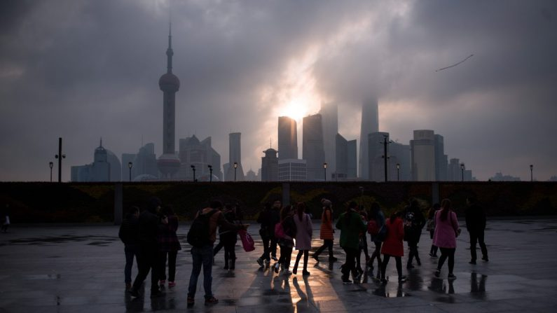 Un grupo de turistas está al lado del Bund, cerca del río Huangpu, en el distrito financiero de Pudong New, en Shanghai, China, el 14 de marzo de 2016. (Johannes Eisele/AFP/Getty Images)