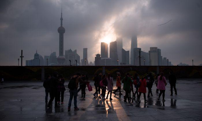Un grupo de turistas junto a la zona del malecón, cerca del río Huangpu, al otro lado del nuevo distrito financiero de Pudong, en Shanghai, China, el 14 de marzo de 2016. (Johannes Eisele/AFP/Getty Images)