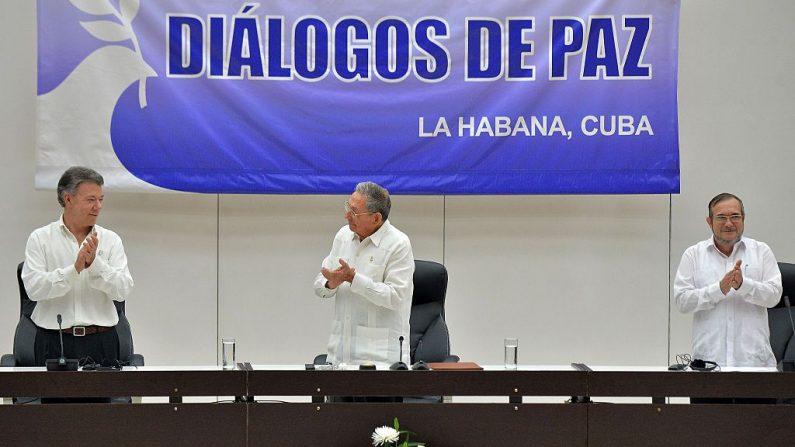"""El presidente colombiano Juan Manuel Santos (izq.), el dictador cubano Raúl Castro (c) y Timoleon Jiménez, alias """"Timochenko"""". (der), jefe de la guerrilla izquierdista de las FARC, aplauden durante la firma del alto el fuego en La Habana el 23 de junio de 2016. (ADALBERTO ROQUE/AFP/Getty Images)"""