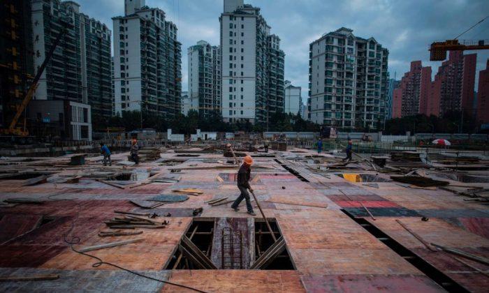 Un hombre trabaja en una obra de construcción de un rascacielos residencial en Shanghai. (JOHANNES EISELE/AFP/Getty Images)
