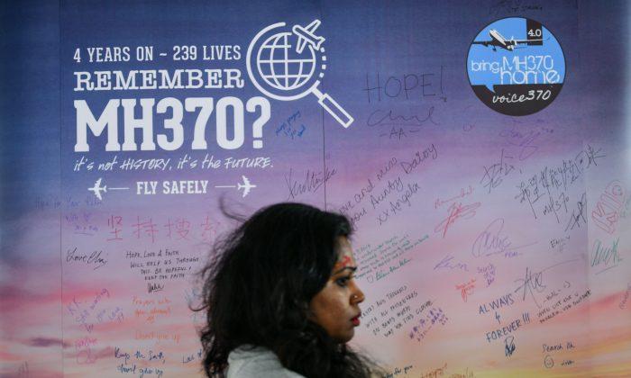 Una mujer pasa junto a una pancarta con mensajes de solidaridad para los pasajeros del desaparecido vuelo MH370 de Malaysia Airlines, durante un acto conmemorativo en Kuala Lumpur el 3 de marzo de 2018. (Manan Vatsyayana/AFP/Getty Images)