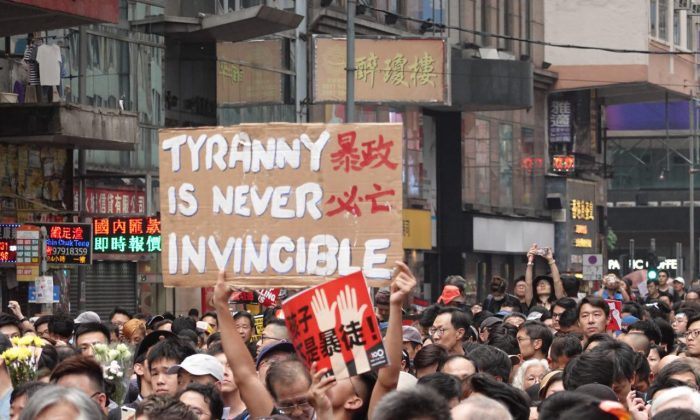 """Un manifestante sostiene un cartel que dice """"La tiranía nunca es invencible""""  en referencia al gobierno de Hong Kong bajo la líder Carrie Lam el 16 de junio de 2019. Otro manifestante sostiene un letrero en rojo con los caracteres chinos """"Los niños no son alborotadores"""". (Yu Gang/La Gran Época)"""