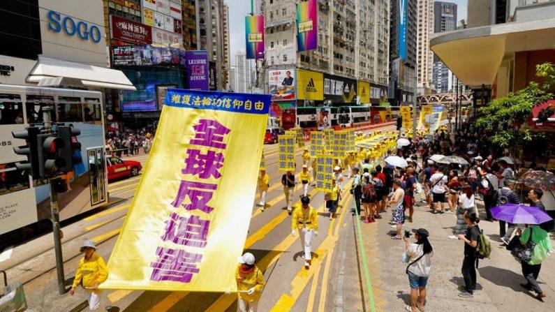 """Los practicantes de Falun Dafa sostienen una pancarta gigante con las palabras """"Oposición global a la persecución"""" en una marcha en Hong Kong el 21 de julio de 2019. (Li Yi/La Gran Época)"""