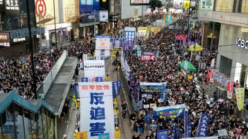 Los practicantes de la disciplina espiritual Falun Dafa participan en la marcha por el aniversario de Hong Kong el 1 de julio de 2019. (Song Bilong/La Gran Época)