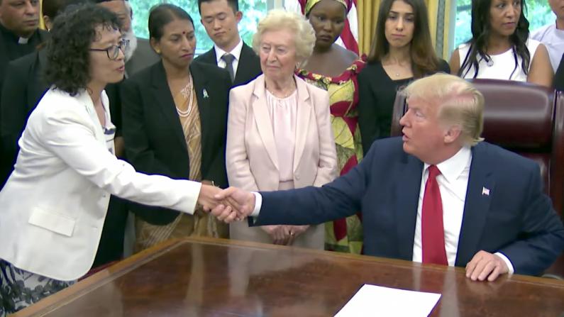 El presidente Donald Trump le da la mano a Yuhua Zhang, una practicante de Falun Gong que sobrevivió a la persecución en China, en la Casa Blanca el 17 de julio de 2019. (Captura de pantalla/Casa Blanca)
