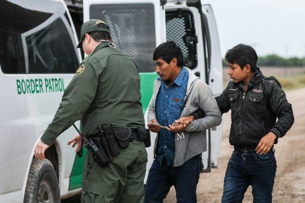 Un agente de la Patrulla Fronteriza detiene a extranjeros ilegales que acaban de cruzar el Río Grande desde México hacia Penitas, Texas, el 21 de marzo de 2019. (Charlotte Cuthbertson/La Gran Época)