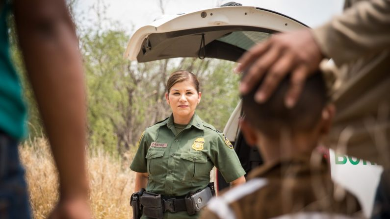 La agente supervisora de la Patrulla Fronteriza, Marlene Castro, habla con un grupo de extranjeros ilegales que acaban de cruzar el Río Grande desde México hacia los Estados Unidos en el Condado de Hidalgo, Texas, el 26 de mayo de 2017. (Benjamin Chasteen/La Gran Época)