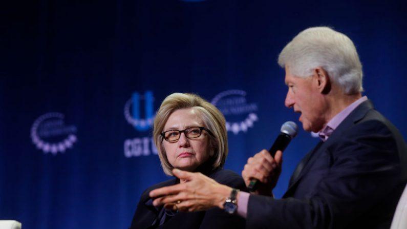 La exsecretaria de Estado Hillary Clinton escucha mientras el expresidente Bill Clinton habla durante la conferencia anual de la Iniciativa Global Clinton en la Universidad de Chicago en Chicago, Illinois, el 16 de octubre de 2018. (Joshua Lott/Getty Images)