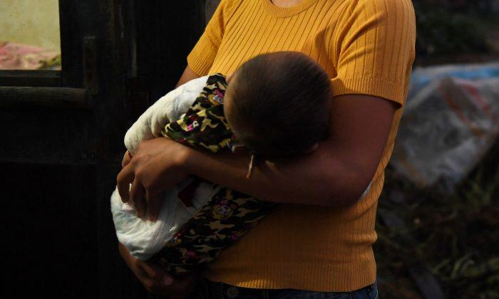 Foto de archivo de una mujer sosteniendo a un bebé. (Greg Baker/AFP/Getty Images)