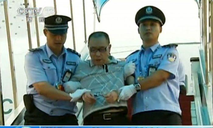 Una captura de pantalla tomada el 23 de julio de 2011 de la Televisión Central de China muestra al empresario chino fugitivo Lai Changx escoltado por la policía después de aterrizar en Beijing a bordo de un vuelo civil bajo la custodia de la policía canadiense. (China's Central Television/STR/AFP/Getty Images)