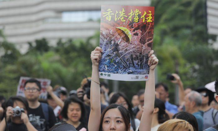 Los manifestantes se reúnen antes de una marcha en la estación de ferrocarril de West Kowloon sosteniendo los afiches del artista canadiense Daxiong Guo, durante una manifestación contra un proyecto de ley de extradición en Hong Kong, el 7 de julio de 2019. (Vivek Prakash/AFP/Getty Images)