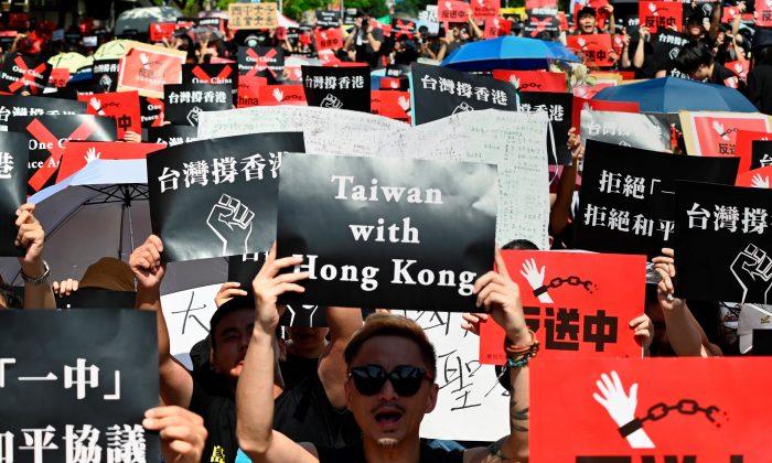 Manifestantes muestran carteles durante una manifestación en apoyo a las continuas protestas en Hong Kong contra la controvertida propuesta de ley de extradición en Taipei, el 16 de junio de 2019. (Sam Yeh/AFP/Getty Images)