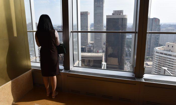 Foto de archivo de una mujer mirando por la ventana de un edificio en China. (Greg Baker/AFP/Getty Images)