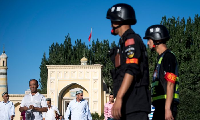 La policía patrulla mientras los musulmanes abandonan la mezquita de Id Kah tras la oración matutina sobre Eid al-Fitr en Kashgar, Xinjiang, China, el 26 de junio de 2017. (Johannes Eisele/AFP/Getty Images)