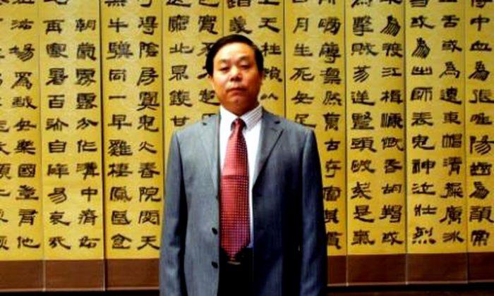 Liu Xitong frente a una de sus obras caligráficas en su exposición. Merodeando entre los que asistían a la exhibición había varios oficiales de policía vestidos de civil. (Minghui.org)