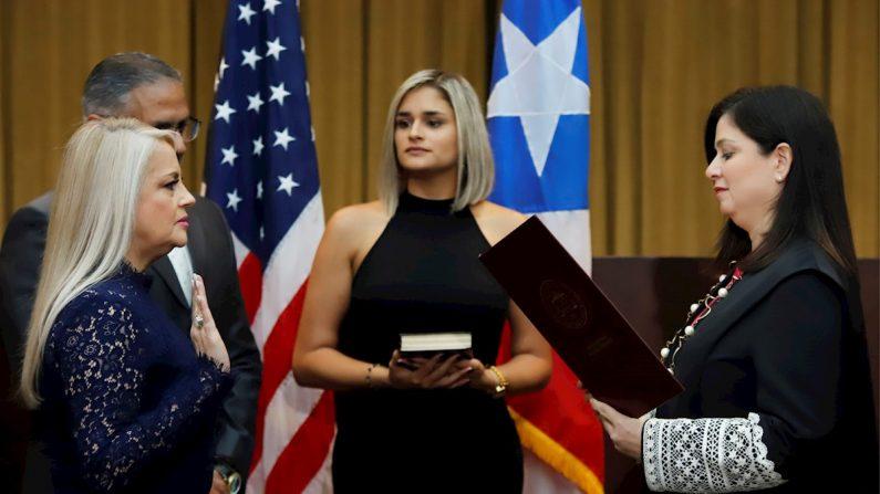 La licenciada Wanda Vázquez Garced (i), juramenta el cargo de gobernadora ante la jueza Presidenta del Tribunal Supremo, Maite Oronoz (d), acompañada de su esposo, el juez Jorge Díaz Reverón (2-i) y su hija Beatriz Díaz (2-d), en San Juan (Puerto Rico). EFE/Thais Llorca