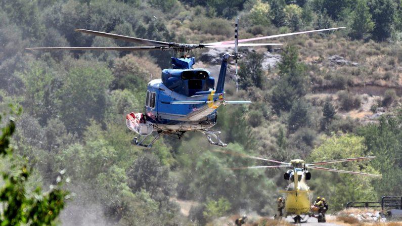 Dos de los helicópteros que participaron en las labores de extinción del incendio forestal declarado en el Real Sitio de San Ildefonso-La Granja, España. EFE/Pablo Martín García