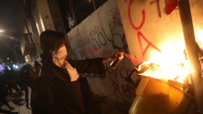 Feministas rompen vidrios y queman papeles al interior de un edificio durante una marcha el 16 de agosto en Ciudad de México, México. (Sashenka Gutiérrez/EFE)