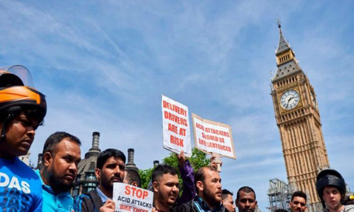Tras una serie de ataques con ácido el 13 de julio, repartidores y motociclistas participan en una manifestación en la Plaza del Parlamento, el 18 de julio de 2017. (NIKLAS HALLE'N/AFP/Getty Images)