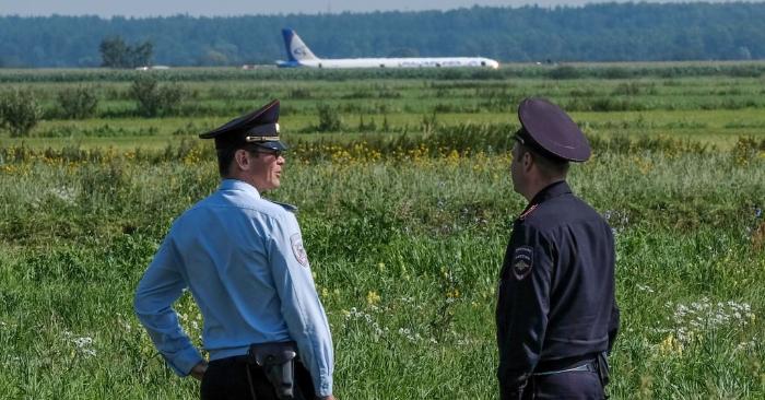 El 15 de agosto de 2019, agentes de policía hacen guardia cerca del lugar de aterrizaje forzoso del avión de Ural Airlines en un campo de maíz cerca del aeropuerto Zhukovsky de Moscú. Foto de YURI KADOBNOV/AFP/Getty Images.