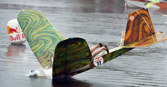 """Un participante aterriza en el agua con su máquina voladora casera durante el """"Red Bull Flugtag"""" (día de vuelo de Red Bull) el 2 de junio de 2013 en Kiev. Foto de SERGEI SUPINSKY/AFP/Getty Images."""