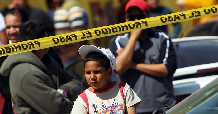 Un niño observa una escena de asesinato en la que dos hombres yacen muertos en Juárez, México. (Foto de Spencer Platt/Getty Images)