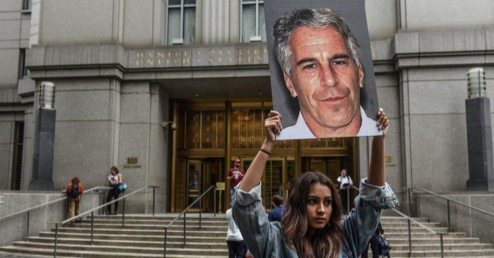 """Un grupo de protesta llamado """"Hot Mess"""" sostiene carteles de Jeffrey Epstein frente al juzgado federal de la ciudad de Nueva York, el 8 de julio de 2019. (Stephanie Keith/Getty Images)"""