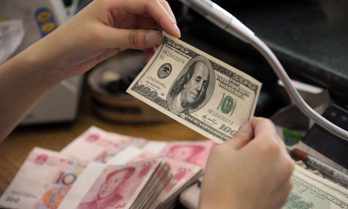 Un empleado bancario chino revisa un billete de 100 dólares estadounidenses junto a unos fajos de billetes de 100 yuanes en una ventanilla bancaria en la ciudad de Hefei, provincia de Anhui, China, el 30 de septiembre de 2010. (STR/AFP/Getty Images)