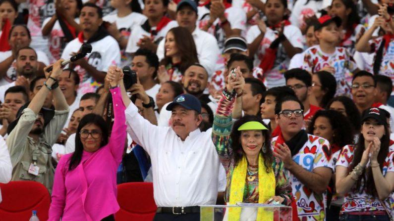 """El presidente nicaragüense Daniel Ortega (C) levanta las manos de su esposa, la vicepresidenta Rosario Murillo (der) y la vicepresidenta venezolana Delcy Rodríguez, durante la conmemoración del 40 aniversario de la Revolución Sandinista en la plaza """"La Fe"""" de Managua el 19 de julio de 2019. (INTI OCON/AFP/Getty Images)"""