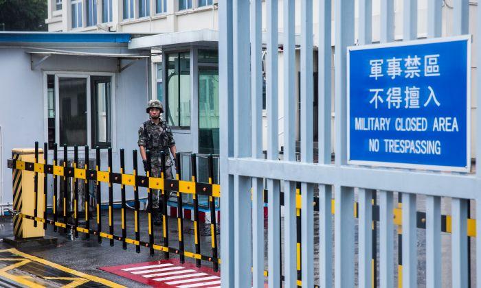 Un soldado del Ejército Popular de Liberación de China (EPL) vigila la entrada del edificio de las Fuerzas del Ejército Popular de Liberación de Hong Kong, que es el cuartel general de la guarnición del EPL de Hong Kong, en el distrito de Admiralty en Hong Kong, el 1 de agosto de 2019. (ISAAC LAWRENCE/AFP/Getty Images)