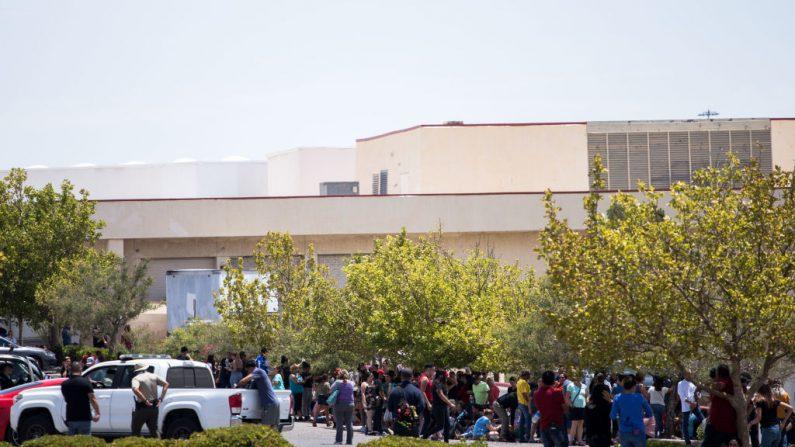 Individuos que fueron evacuados se sientan en un estacionamiento frente al WalMart donde ocurrió el tiroteo en el Centro Comercial Cielo Vista en El Paso, Texas, el sábado 3 de agosto de 2019. (Foto de JOEL ANGEL JUAREZ/AFP/Getty Images)