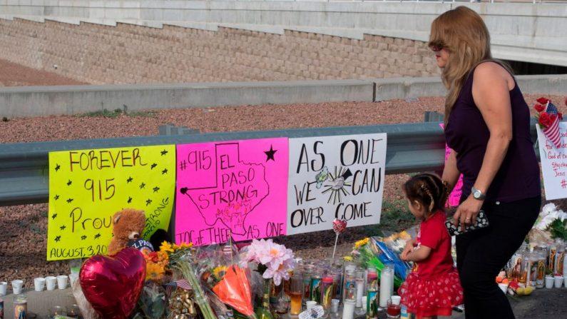 Una familia camina junto a flores y letreros en un monumento improvisado después del tiroteo que dejó 22 personas muertas en el Cielo Vista Mall WalMart en El Paso, Texas, el 5 de agosto de 2019. (MARK RALSTON/AFP/Getty Images)