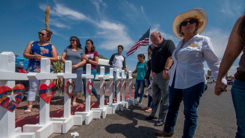 La gente reza junto a cruces con los nombres de las víctimas que murieron en el tiroteo a un monumento improvisado después del tiroteo que dejó 22 personas muertas en el Centro Comercial Cielo Vista WalMart en El Paso, Texas, el 5 de agosto de 2019. (MARK RALSTON/AFP/Getty Images)