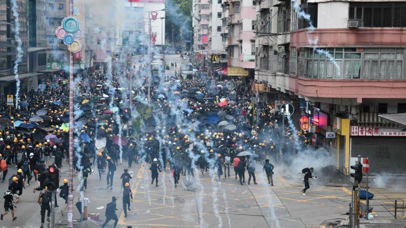 Los manifestantes en favor de la democracia arrojan gases lacrimógenos disparados por la policía durante una manifestación contra el controvertido proyecto de ley de extradición en el distrito de Sham Shui Po en Hong Kong el 11 de agosto de 2019. (Anthony Wallace/AFP/Getty Images)