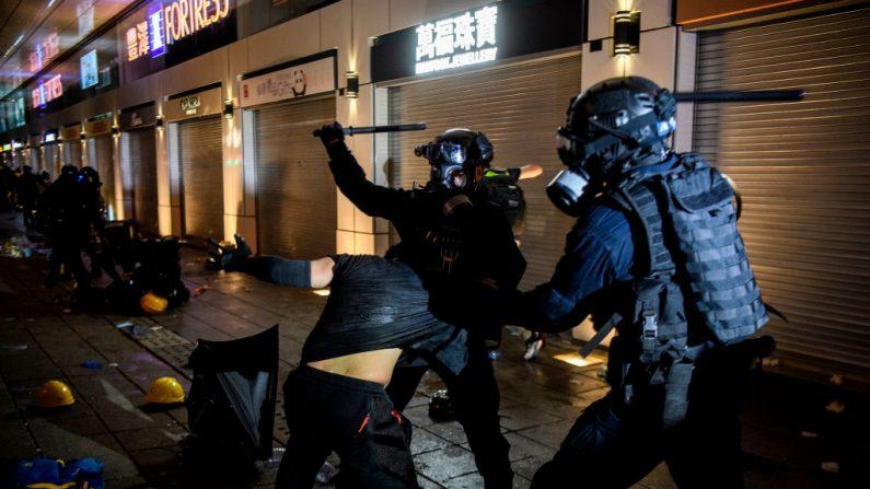 La policía arresta con violencia a un hombre durante las protestas en Tsim Sha Tsui en Hong Kong el 11 de agosto de 2019, en la última oposición a una planificada ley de extradición de Beijing, que rápidamente se convirtió en un movimiento más amplio para reformas democráticas. Miles de manifestantes en favor de la democracia salieron a las calles de Hong Kong por décimo fin de semana consecutivo el 11 de agosto, desafiando nuevamente a la policía que disparó descargas de gases lacrimógenos en varios lugares. (ANTHONY WALLACE / AFP / Getty Images)