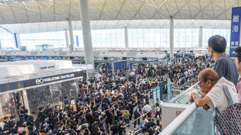 Los manifestantes a favor de la democracia en Hong Kong (C) abarrotan el área frente a las puertas de embarque para bloquear el acceso durante otra manifestación en el aeropuerto internacional de Hong Kong el 13 de agosto de 2019. (PHILIP FONG / AFP / Getty Images)