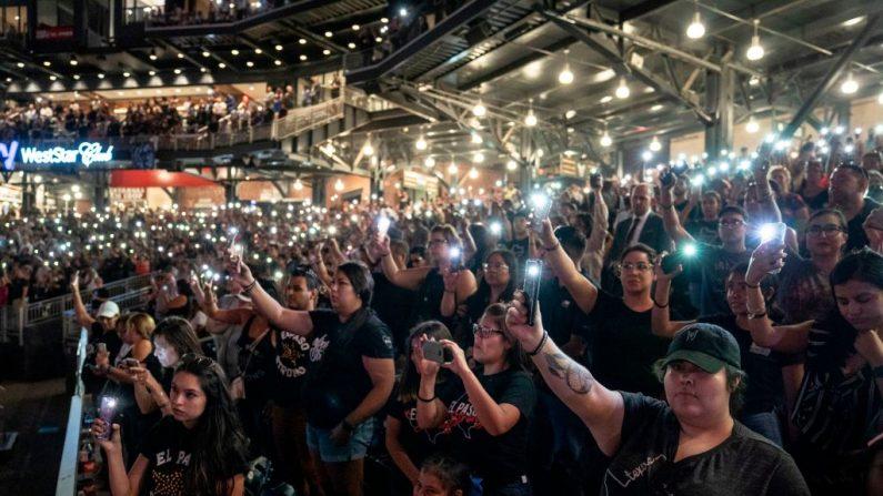 Los asistentes sostienen las linternas en sus teléfonos durante un servicio en memoria de las 22 víctimas del tiroteo masivo en el Southwest University Park en El Paso, Texas, el 14 de agosto de 2019. (PAUL RATJE/AFP/Getty Images)