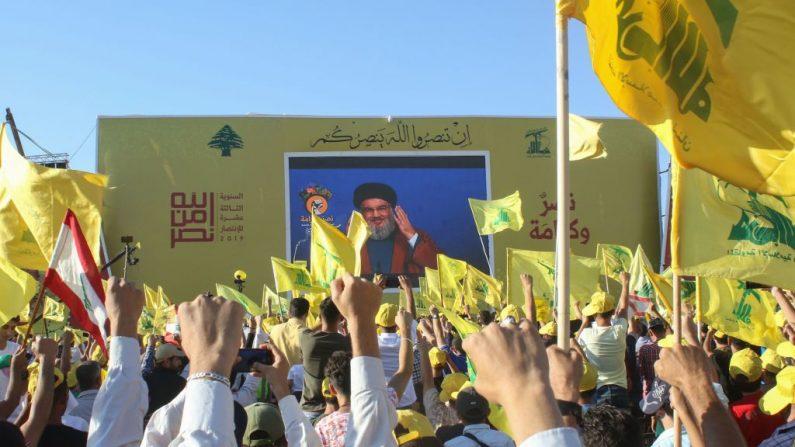 Los partidarios del movimiento militante chiíta libanés Hezbolá ondean la bandera del grupo durante una conmemoración del 13º aniversario del fin de la guerra de 2006 con Israel en la ciudad libanesa de Bint Jbeil, en el sur del Líbano, el 16 de agosto de 2019. (MAHMOUD ZAYYAT/AFP/Getty Images)