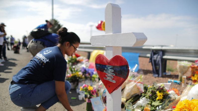 Una mujer se arrodilla en un monumento improvisado a las afueras de Walmart, cerca de la escena del tiroteo en masa que dejó a 22 personas muertas, el 5 de agosto de 2019, en El Paso, Texas. (Mario Tama/Getty Images)