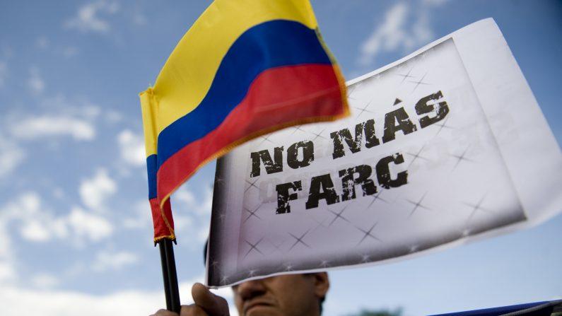 """Un hombre sostiene una bandera nacional colombiana y una pancarta que dice """"No más FARC"""" mientras espera la llegada de un grupo de motociclistas que participan en la """"Caravana por la Libertad"""" el 23 de noviembre de 2011 en Cali, Colombia. (Luis Robayo/AFP/Getty Images)"""