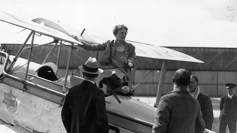 24 de junio de 1928: La aviadora estadounidense Amelia Earhart (1898-1937) hablando con amigos desde la cabina de su Moth el día de su viaje a Northolt. (Topical Press Agency/Getty Images)
