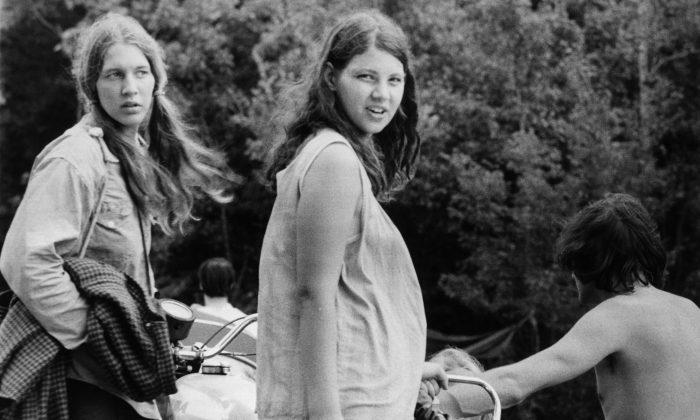 Agosto de 1969: Una mujer embarazada y su amiga esperan mientras se preparan para irse de la granja Bethil de Max Yasgur y el festival de música de Woodstock. (Three Lions/Getty Images)
